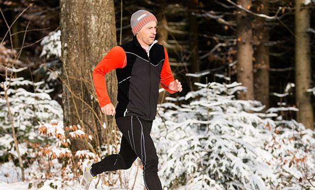 A runner training next to a forest covered in snow